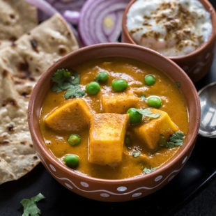 matar paneer in a clay bowl with a bowl of yogurt on the side and some rotis in the back
