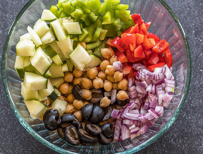 bowl with chickpeas, chopped onion,olives, cucumber and pepper