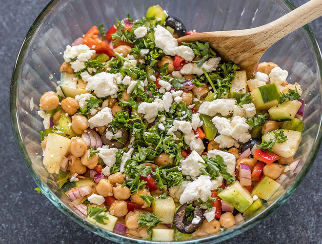 bowl with chickpeas, chopped onion,olives, cucumber, pepper, parsley and feta cheese