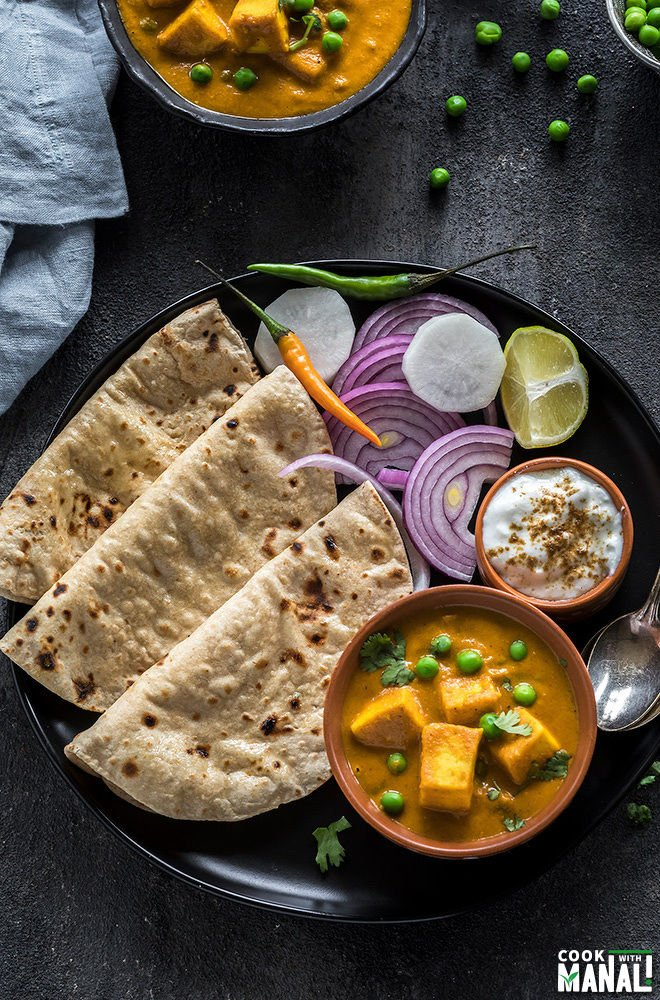 a black plate with a bowl of matar paneer, fresh rotis, bowl of yogurt and a side of salad