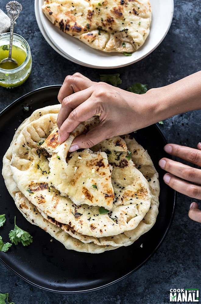 pair of hands taking a bite off homemade garlic naan