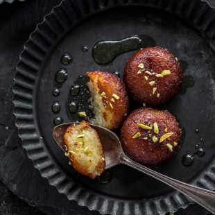 3 pieces of gulab jamun, with one being cut in half, garnished with pistachios served on a round black plate