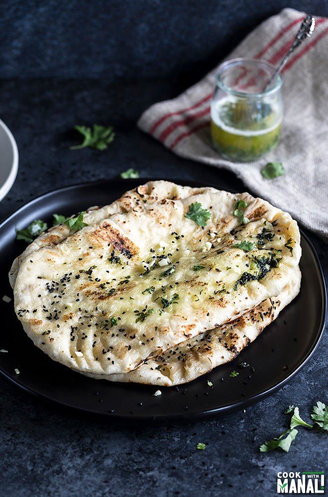 homemade garlic naan arranged in a black plate with a piece of fabric in the background
