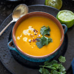 Thai Butternut Squash Soup served in a blue bowl with squeezed lime on the side