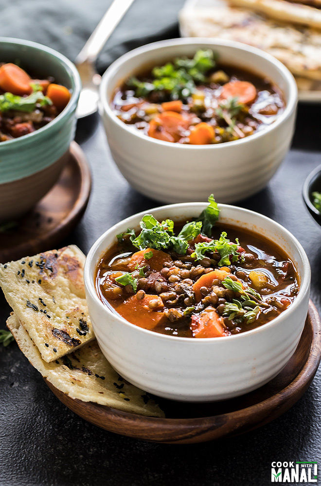 vegan lentil soup in a white bowl with bread on the side and more bowls of lentil soup on the side and back