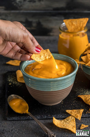 a hand dipping chips into a bowl of vegan cheese sauce made in the instant pot