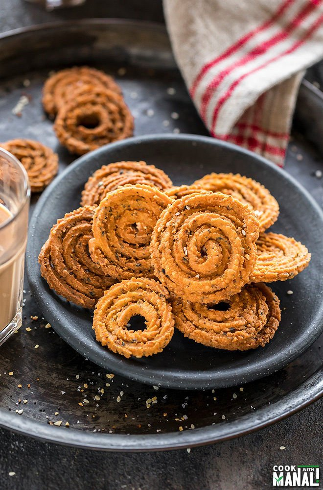 chakli on round black plate with a glass of chai on the side