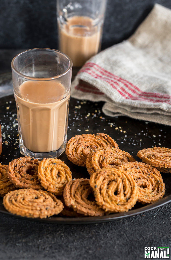 homemade instant chakli on a plate with a glass of chai in the background