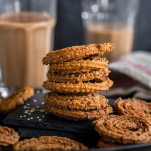 stack of chakli on a black plate and glasses of chai in the background