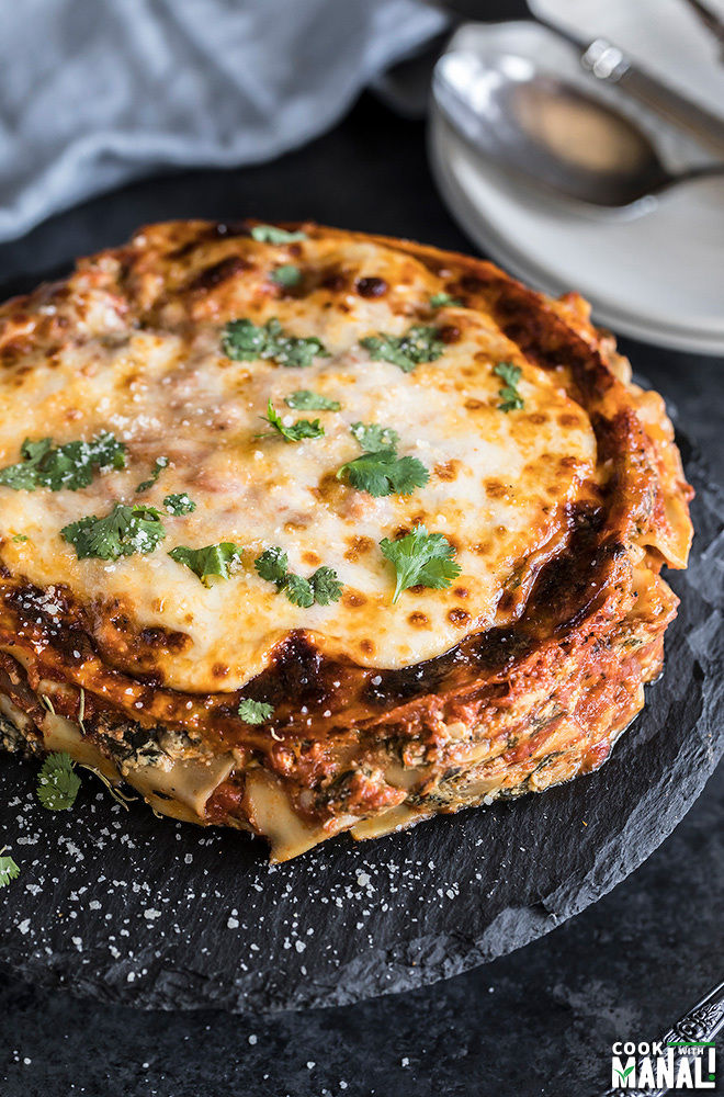 spinach mushroom lasagna on a round black serving board with a napkin and plates in the background