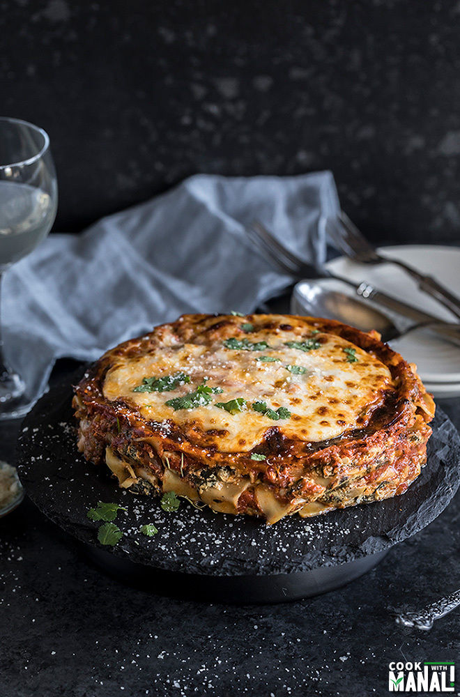 spinach mushroom lasagna on a round black serving board with a napkin and glass in the background