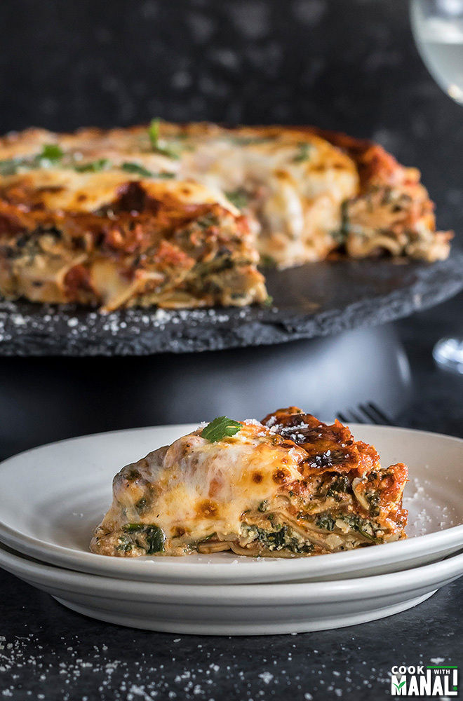 a piece of spinach mushroom lasagna served in a white plate with the whole lasagna in the background