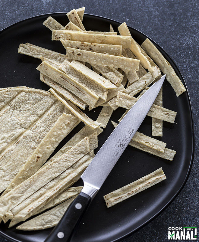 black plate with cut corn tortillas along with a knife