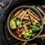 instant pot vegetarian tortilla soup in a bowl topped with tortilla strips, avocado, cilantro, lime wedge and jalapenos