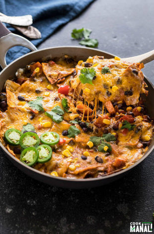 one-pot vegetarian enchiladas in a skillet with a spatula lifting of the cheese