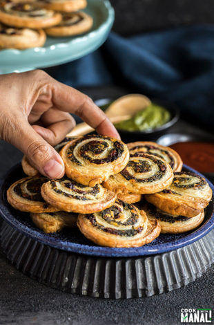 hand holding one of the puff pastry pinwheels from a blue plate