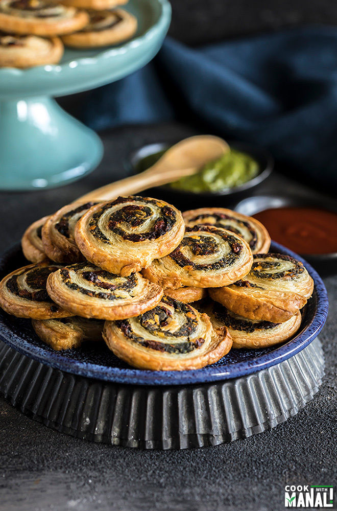 spinach & sun-dried tomato puff pastry pinwheels stacked on a blue plate with black bowls filled with chutney & ketchup in the background