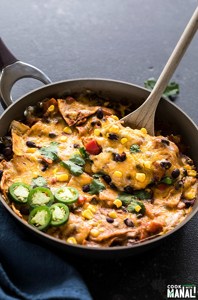 one-pot vegetarian enchiladas in a skillet with a spatula and garnished with cilantro and jalapenos