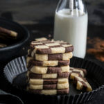 stack of checkerboard cookies with a bottle of milk in the background