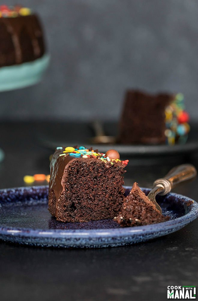 slice of eggless chocolate cake in a blue plate with a fork on the side with another plate and cake stand in the background