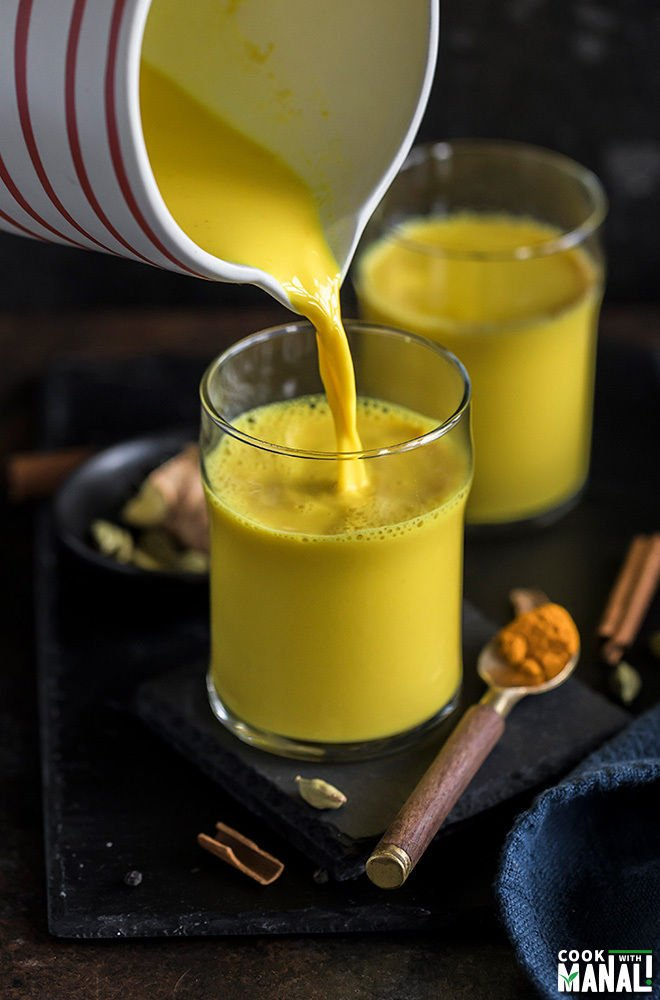 golden milk being poured from a jug into a glass with another glass in the background and a spoon full of turmeric on the side
