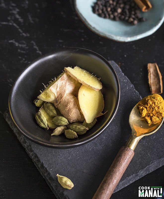 a small black bowl with ginger and cardamom and a spoon with turmeric on the side