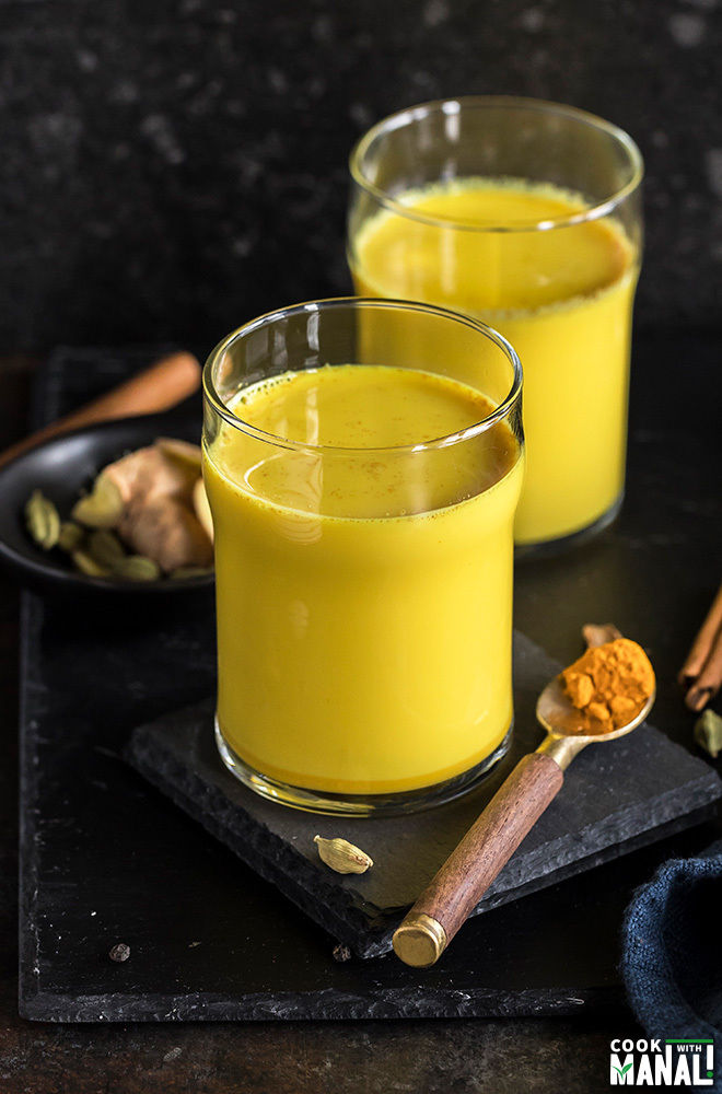 haldi doodh aka golden milk in a glass with another glass in the background and a spoon with turmeric on the side