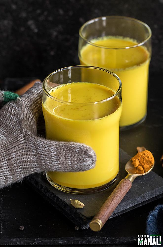 hand wearing a glove holding a glass of golden milk (haldi doodh)