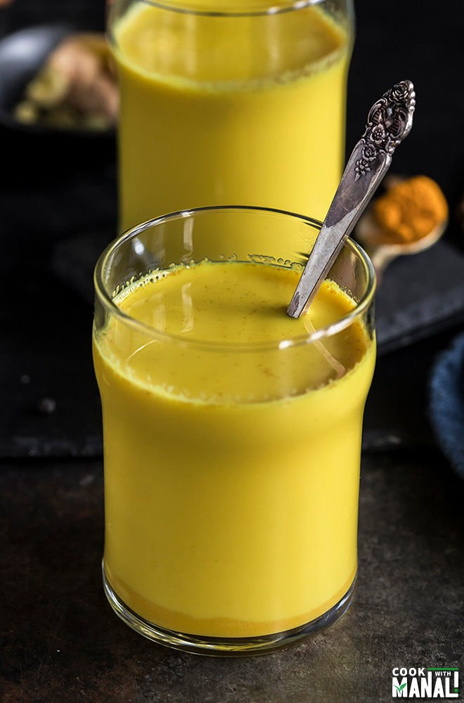 glass of golden milk with a spoon with another glass in the background