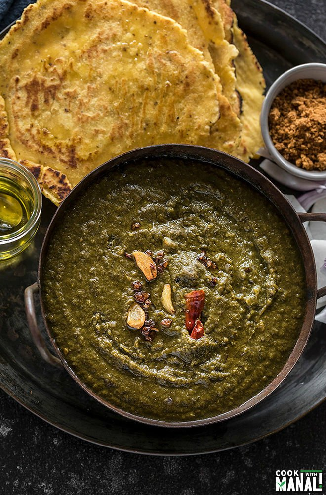 sarson ka saag served in a iron kadhai with makki roti, jaggery and ghee on the side