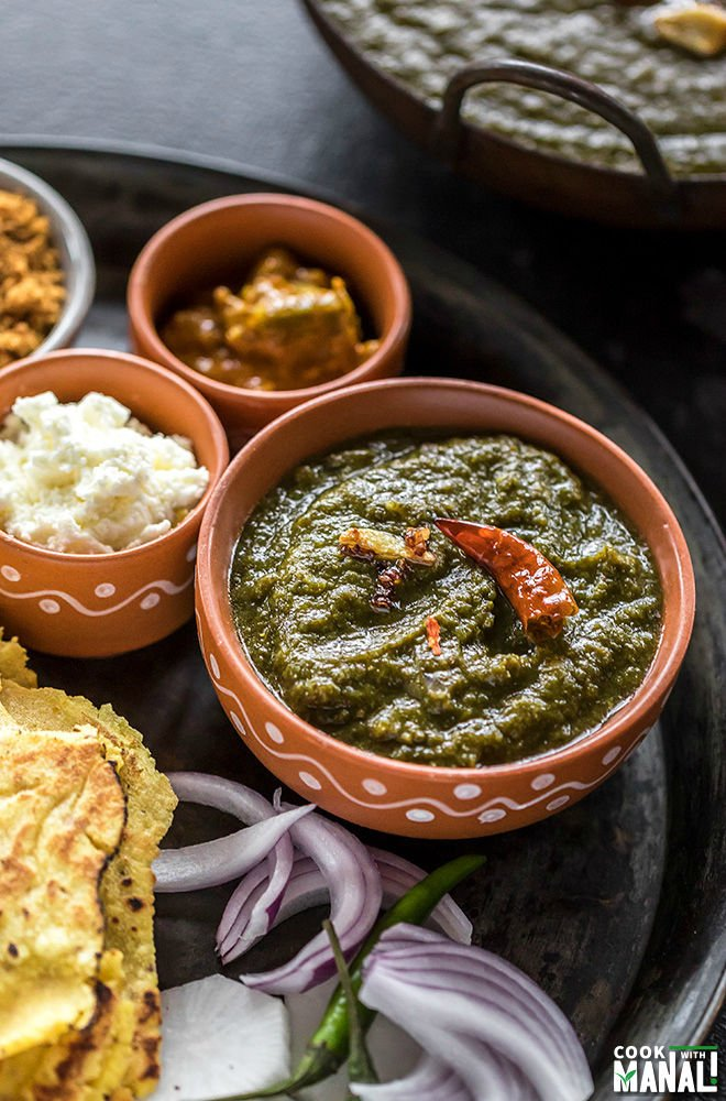sarson ka saag in a small clay bowl with several other bowls filled with pickle, butter, jaggery
