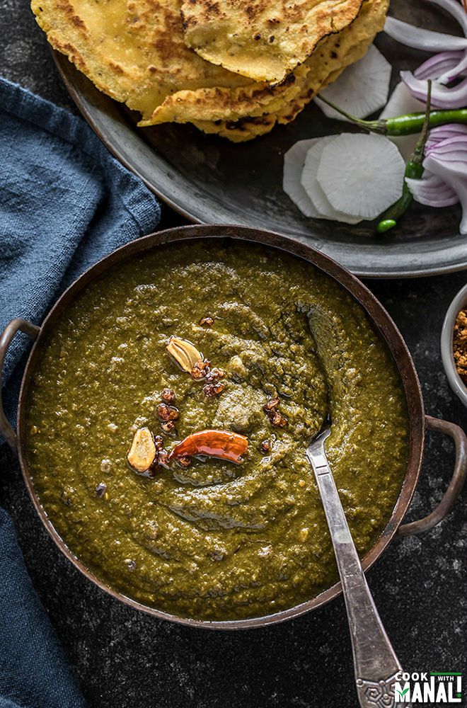sarson ka saag served in a iron kadhai with makki roti and sliced radish and green chilies