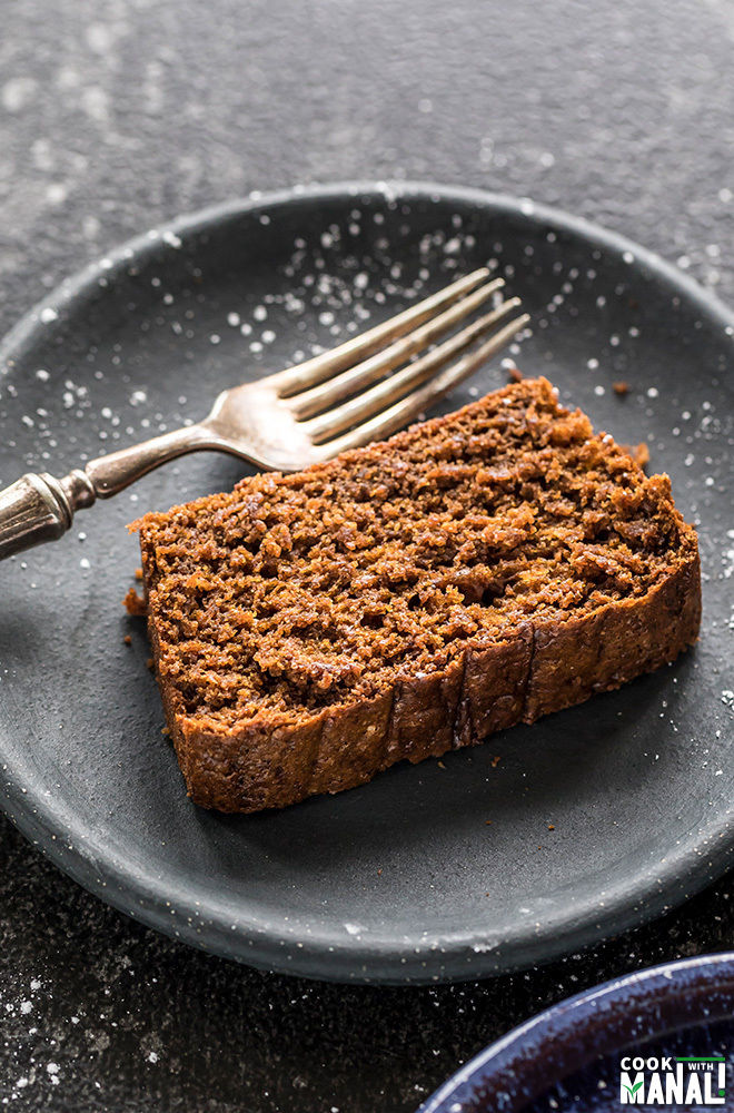 sliced of vegan gingerbread cake in a round black plate with a fork