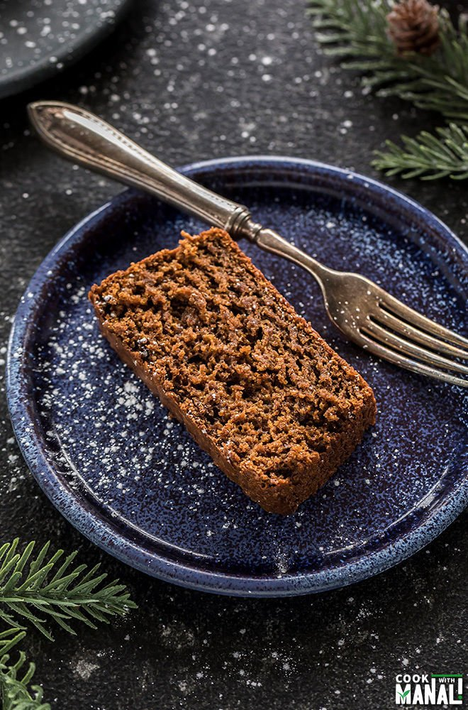 slice of vegan gingerbread cake in a blue plate with a fork on the side
