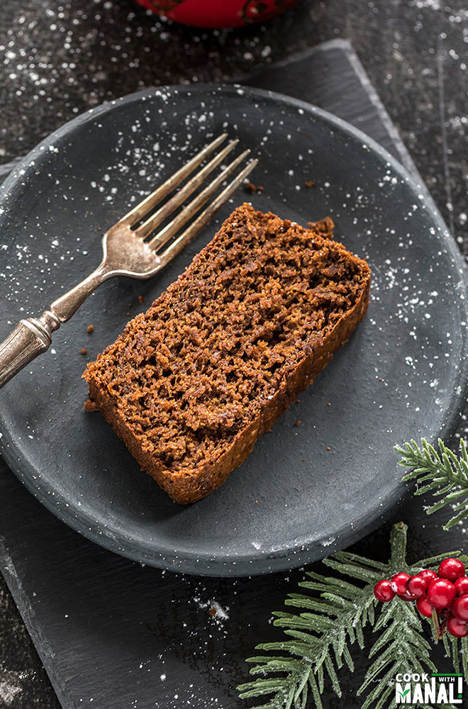 sliced of vegan gingerbread cake in a round black plate with a fork and festive decor on the side