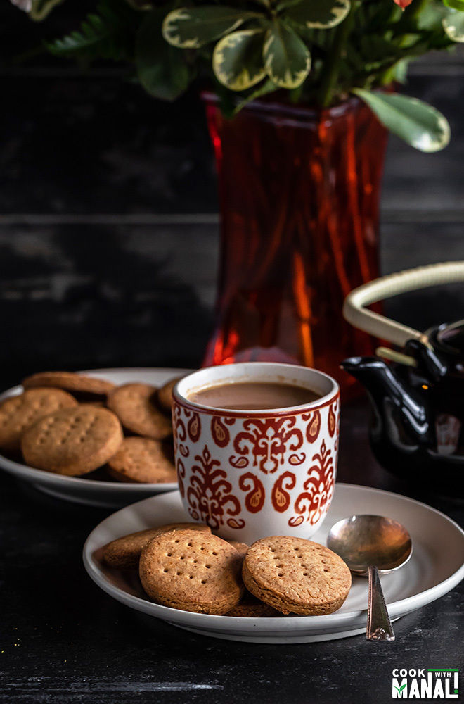 jaggery cookies with a cup of chai on side, teapot in the background