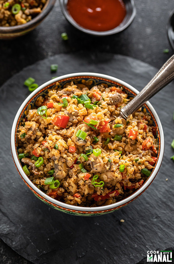bowl of cauliflower fried rice with a spoon