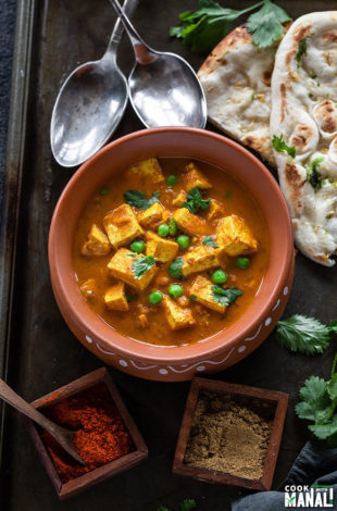 tofu matar served in a round clay pot with naan and spoons in the background and spice boxes on the side