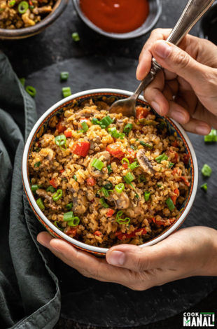 a hand holding a bowl of mushroom cauliflower fried rice from one side and digging into the bowl with a spoon from the other side
