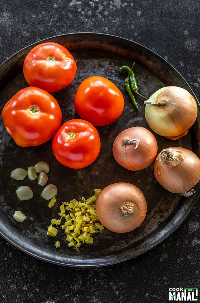 onion, tomato, garlic, ginger and green chilies placed on a round black tray