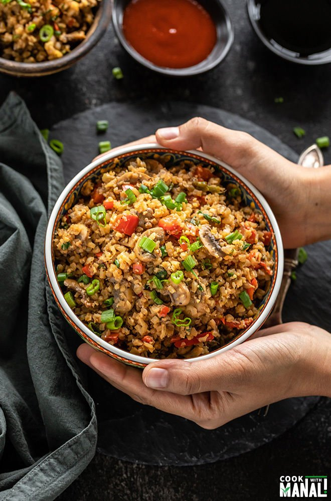 pair of hands holding a bowl of mushroom cauliflower fried rice with napkin on the side and sauce bowls in the back