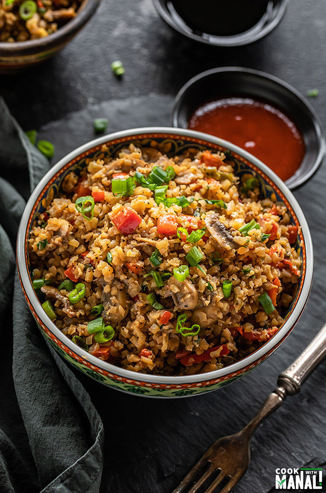 bowl of vegan cauliflower fried rice with a napkin on the side and bowls filled with sauces in the background