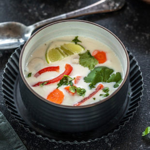 vegan tom kha gai in a black bowl placed in a black rimmed plate with a spoon in the background and some cilantro on the side