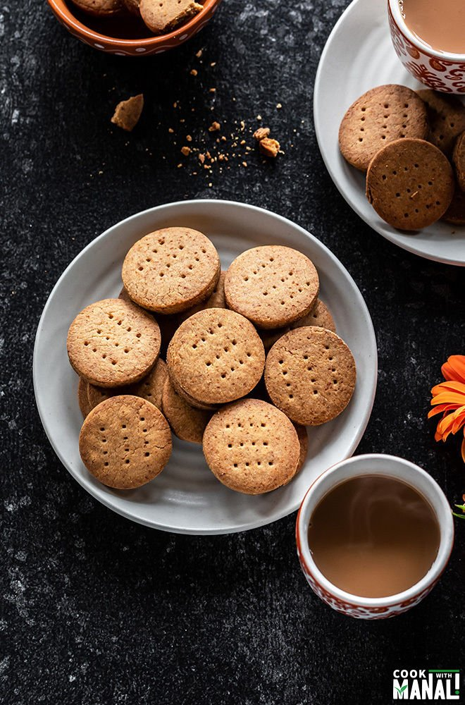 whole wheat jaggery cookies in a white plate with cups of chai on the side