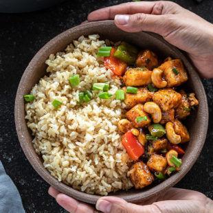 pair of hands holding a bowl of honey cashew tofu