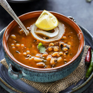 black eyed pea curry in a blue bowl with a lemon wedge and a ring of onion