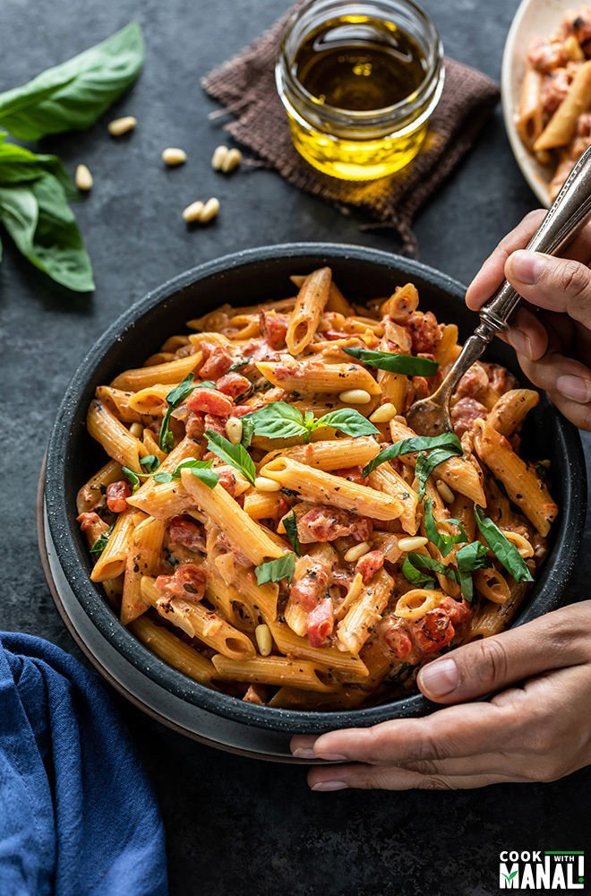 tomato basil pasta in a bowl with a fork digging in into the bowl. There are also some basil leaves and a small jar of olive oil in the background
