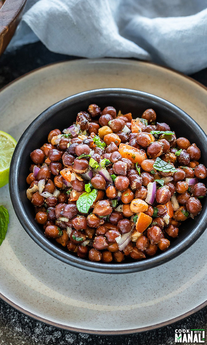a black bowl full of kala chana chaat with a lime wedge and mint leaf on the side