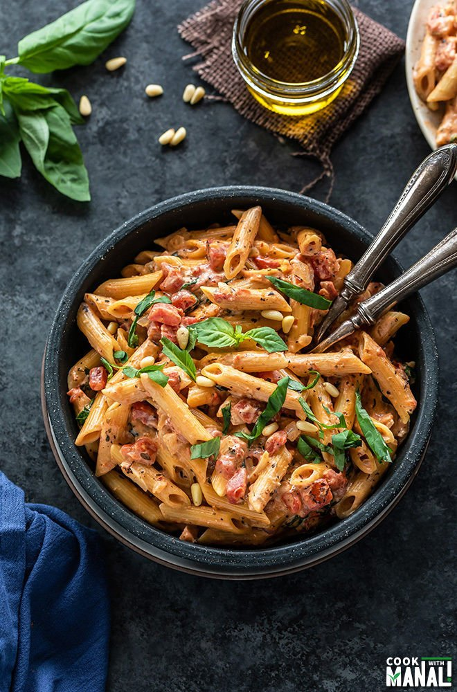 tomato basil pasta in a black bowl with 2 forks. There are also some basil leaves and a small jar of olive oil in the background