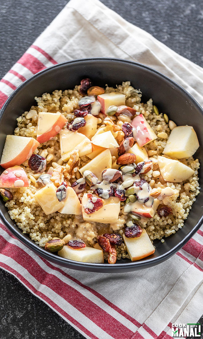 a bowl of quinoa salad with apples, nuts